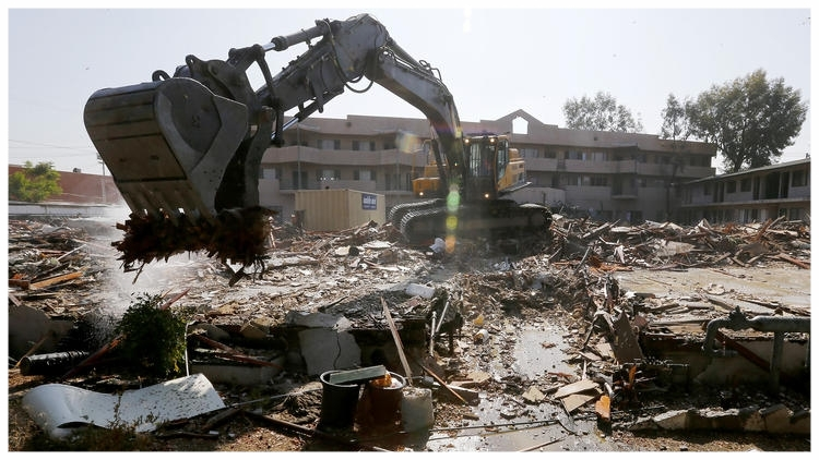 A heavy equipment operator demolishes the former Fiesta Motel in North Hollywood on Thursday. The motel served for 30 years as housing for some of the San Fernando Valley's homeless. (Luis Sinco/Los Angeles Times)