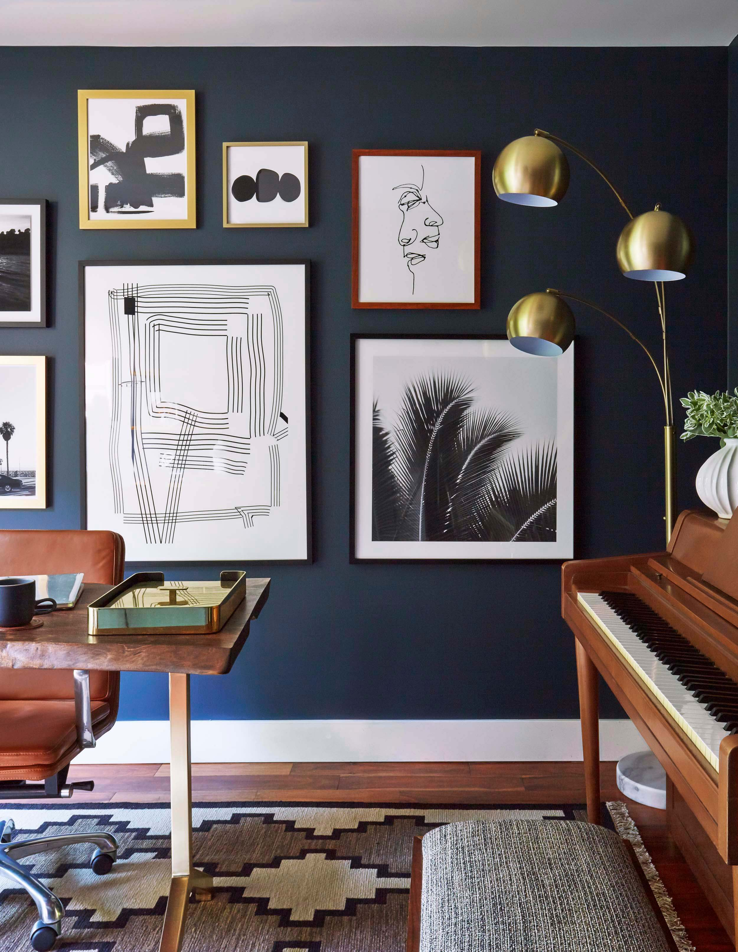 The brass finish of this lamp is picked up in the brass tray and legs of the desk, as well as the gold frames against the dark wall. This use of the lamp is anything but incidental. It's carefully thought out and even works up a beautiful rhythm of curves with the palm tree in the image beside it. Image courtesy Ginny Macdonald Design.