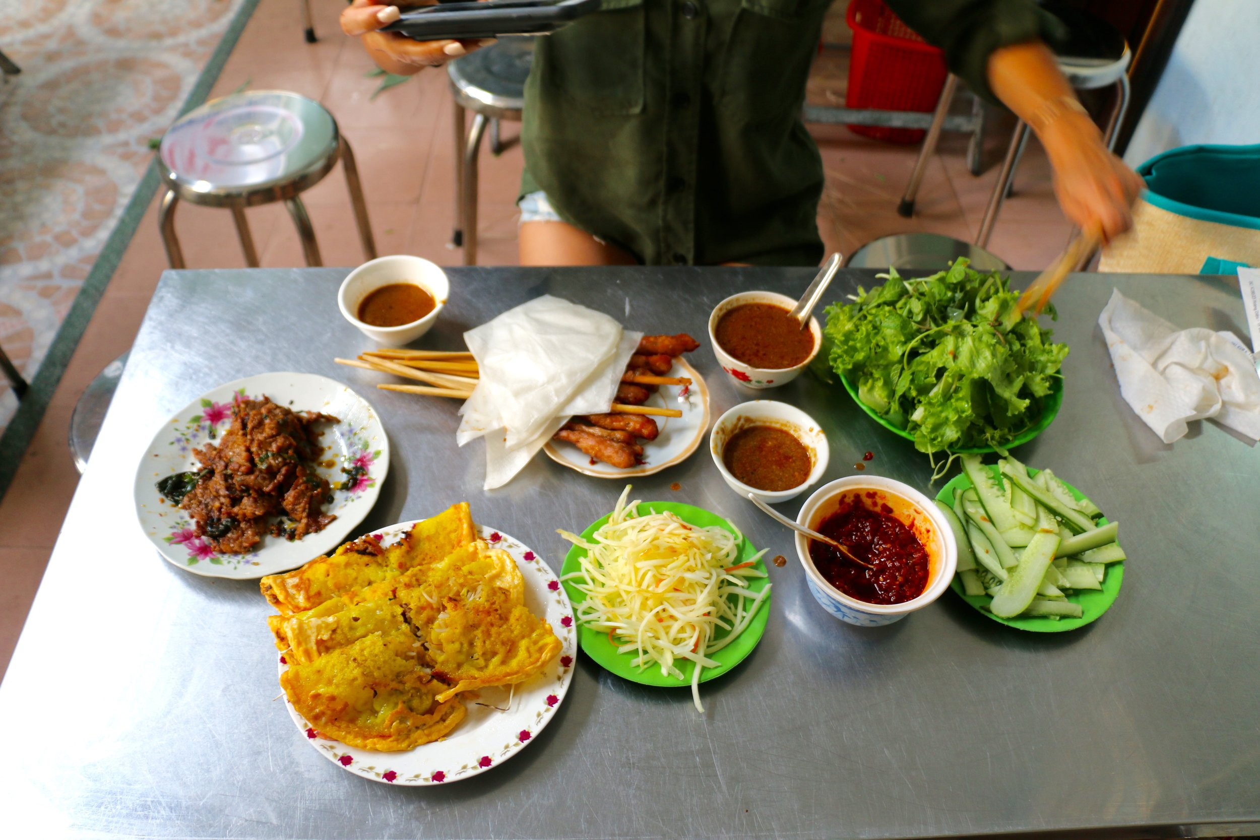 """There really isn't a menu here. You walk in expecting Bahn Xeo (Savory Turmeric Crepes) paired with the """"works."""" There's fresh rice paper skin, crispy crepes, fragrant grilled meats, fresh herbs, hot sauce, dipping sauces...your senses come alive here!"""