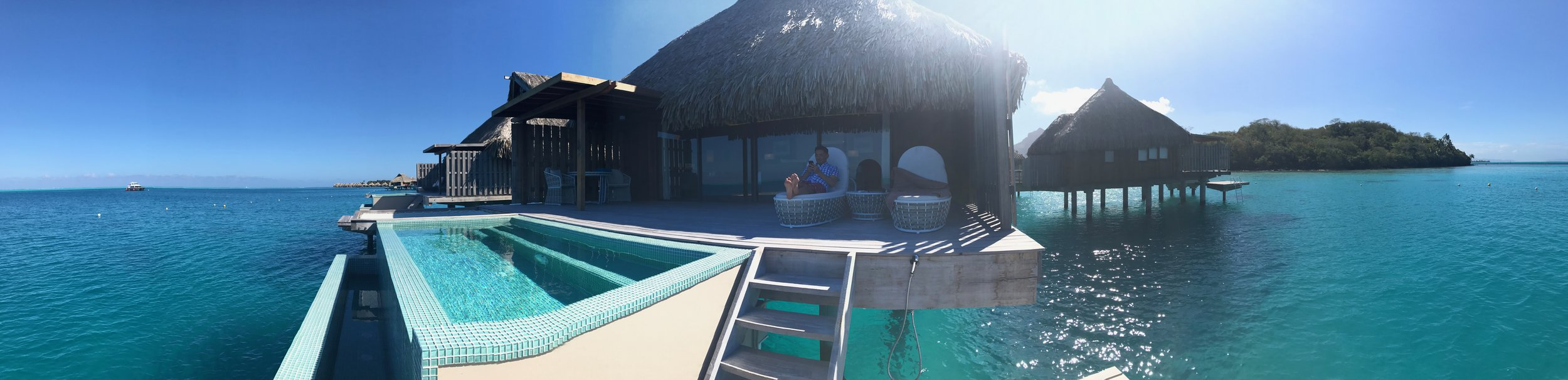 A panorama shot of our villa and my husband sitting on our deck.
