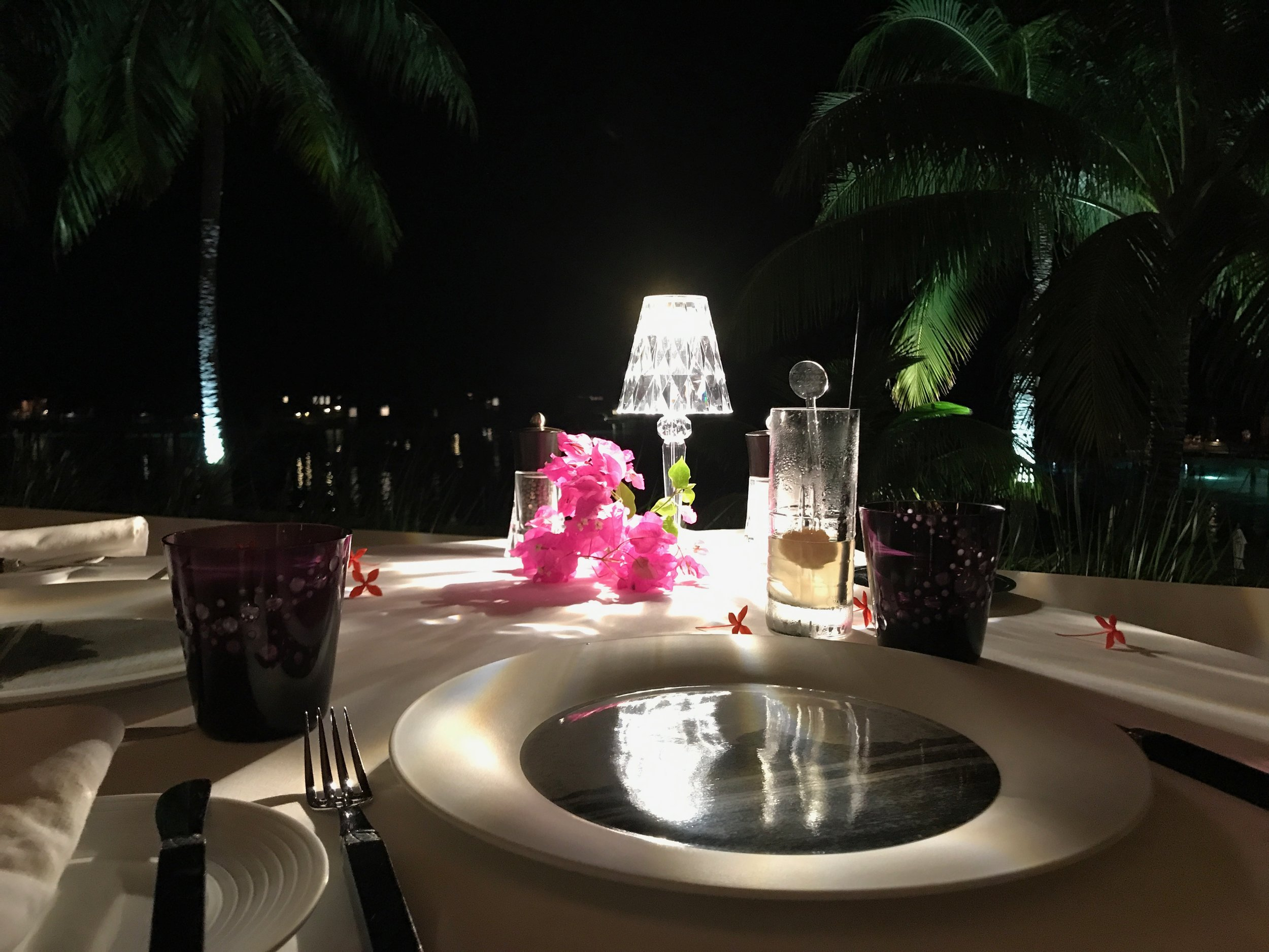 Request a romantic table on the terrace with a view of the water at night at the Iriatai