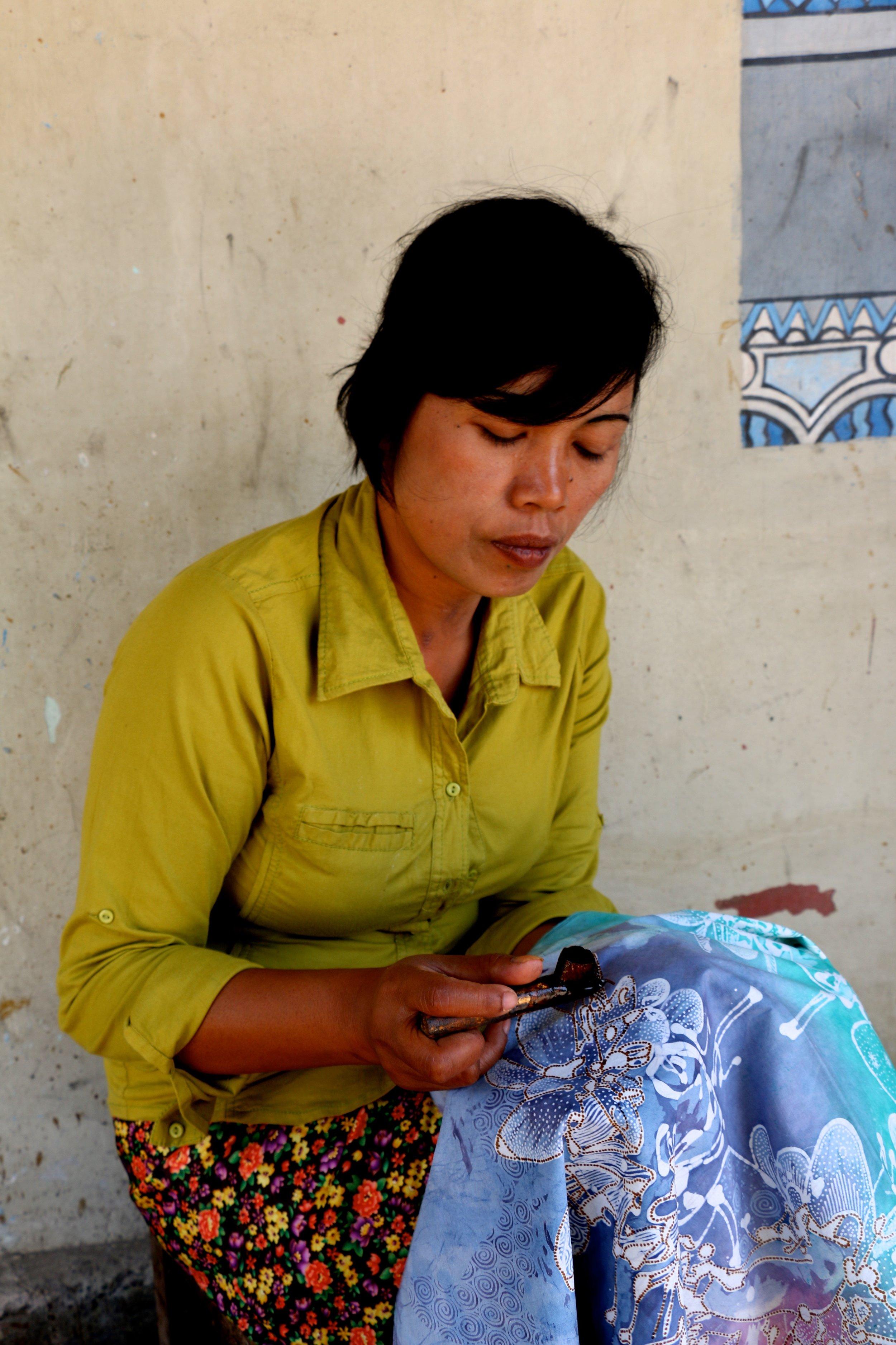 A woman working on batik