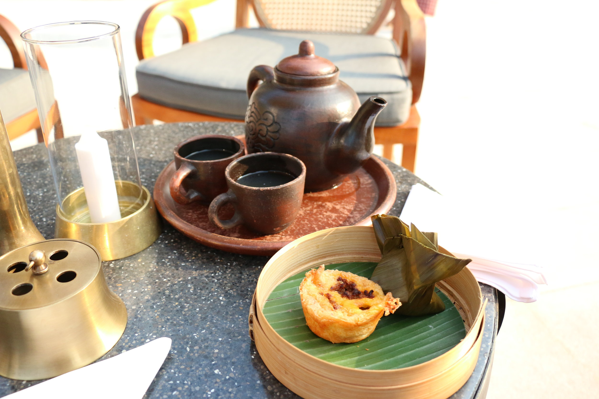 Our tea, a savory pastry filled with some kind of meat filling and a banana leaf wrapped steamed cake made from rice flour and dates
