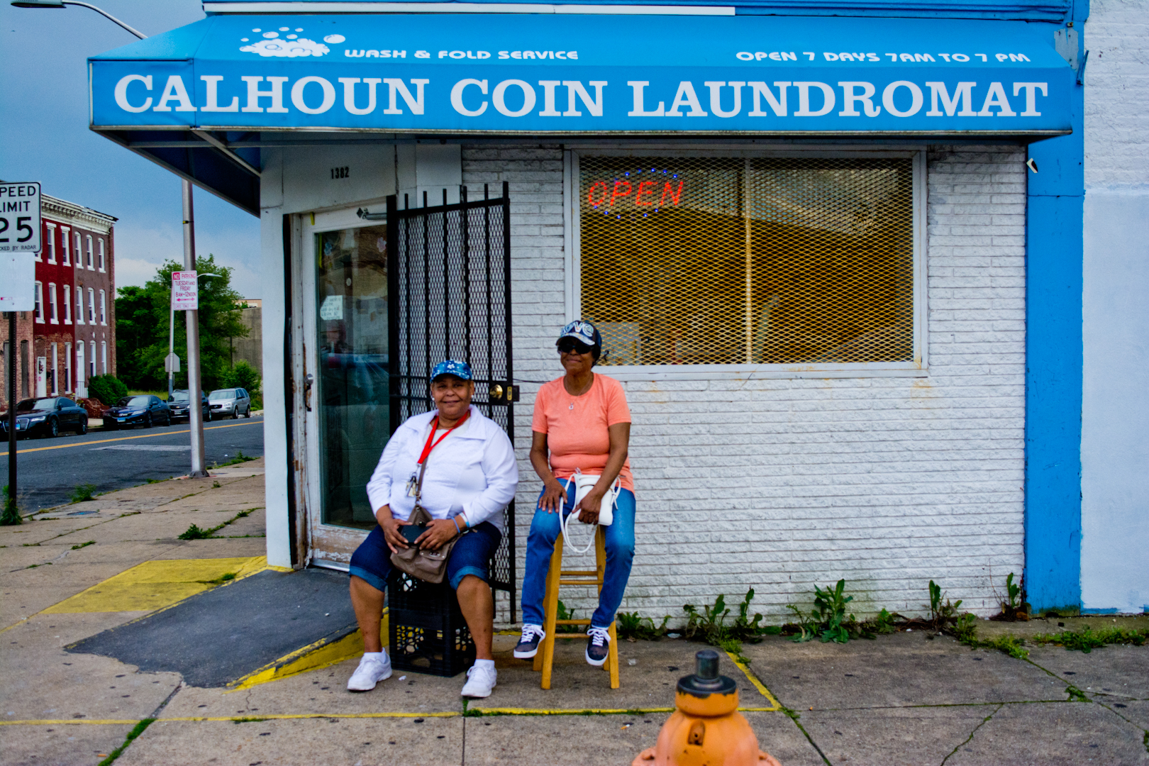"""Talk about the neighborhood!  Oh no! Let's not talk about that!  *laughter*  I've been working at this laundromat for eight years. We have specials Wednesdays and Fridays. We're called the Calhoun Coin Girls. Open seven days a week."""