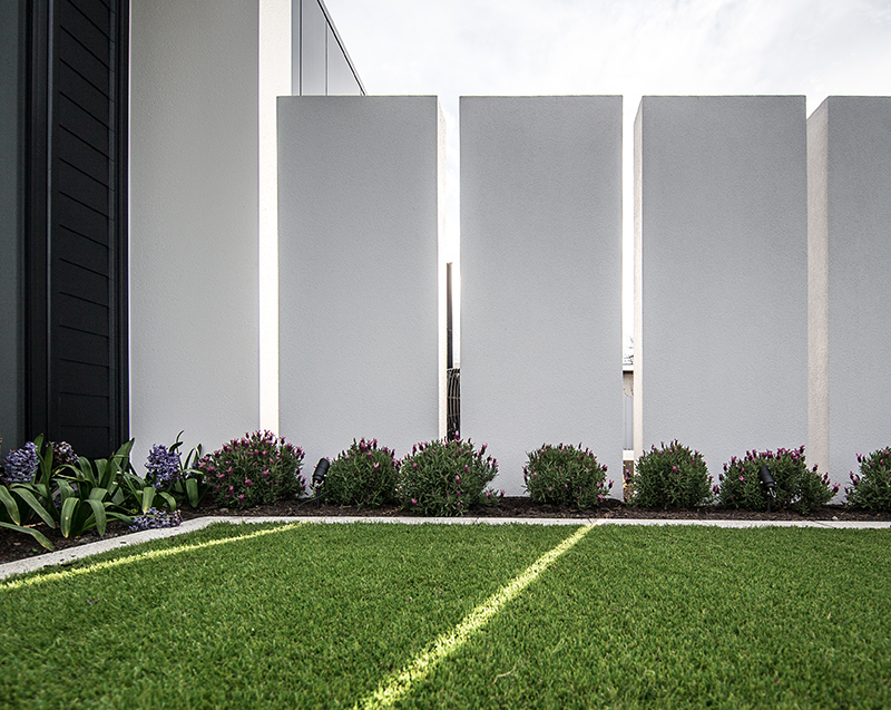 For maximum impact and minimal effort, a lush green carpet of artificial turf provides an area for lounging, while a deck made from a recycled HDPE composite creates a hard-wearing, fade-resistant, non-slip dining area off the interior living room.