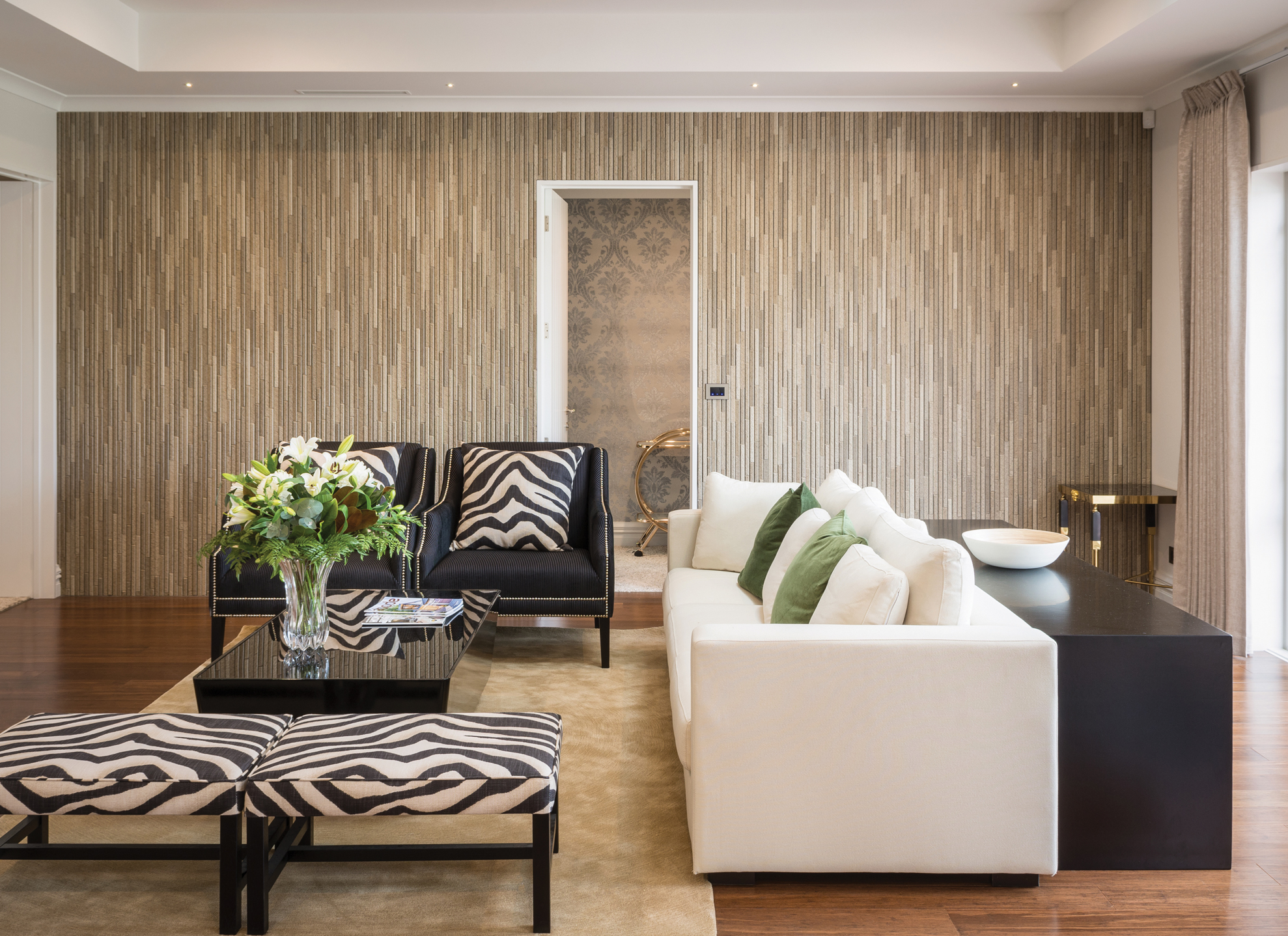 LIVING ROOM:  The textured wall tiles installed by J & C Tiling give this home an opulent and classic feel.