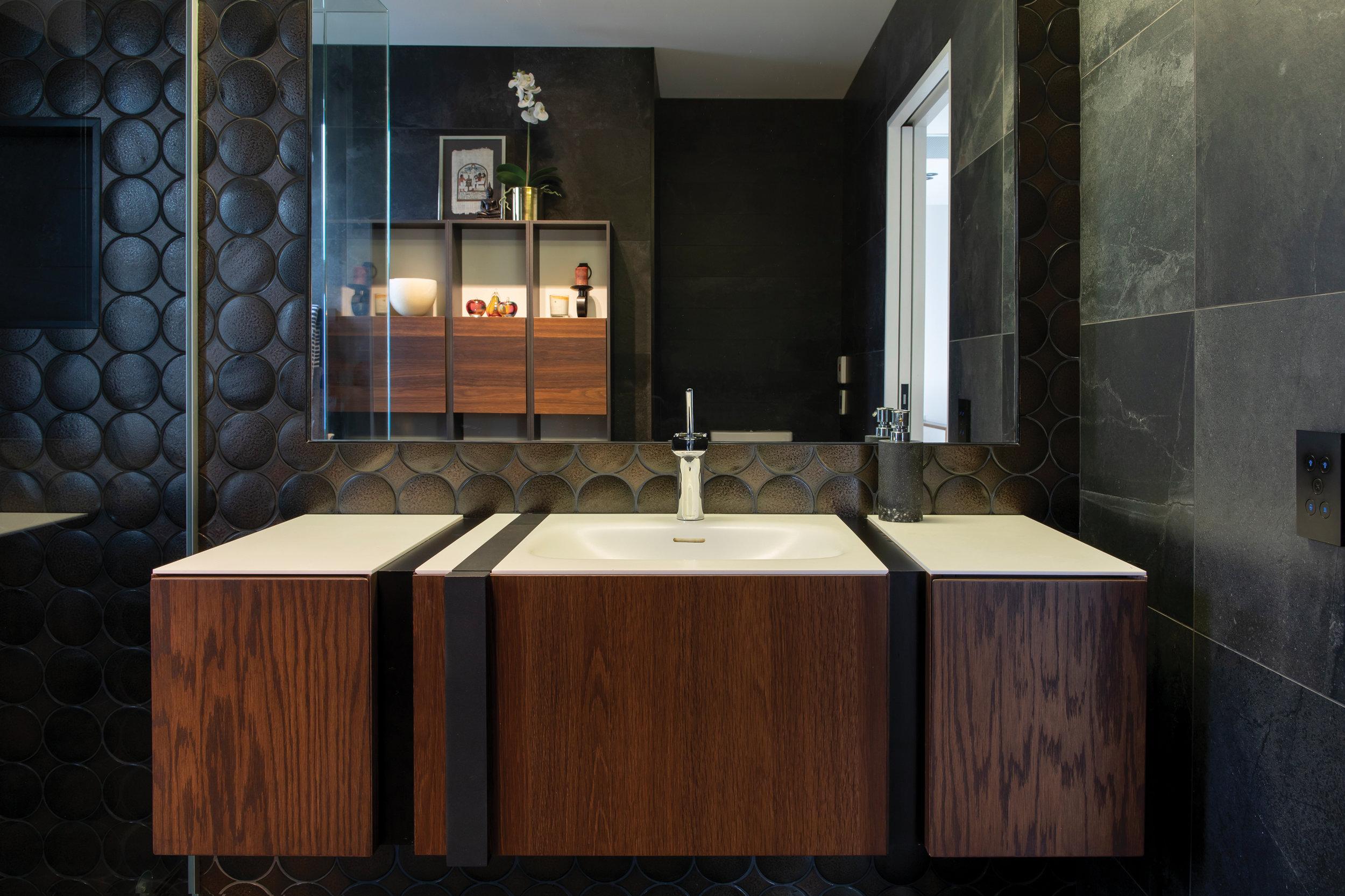 BATHROOM:  Lens Jewel 205 x 400 sheets create a stunning dark bathroom, with Porcelanosa vanity and shelving.