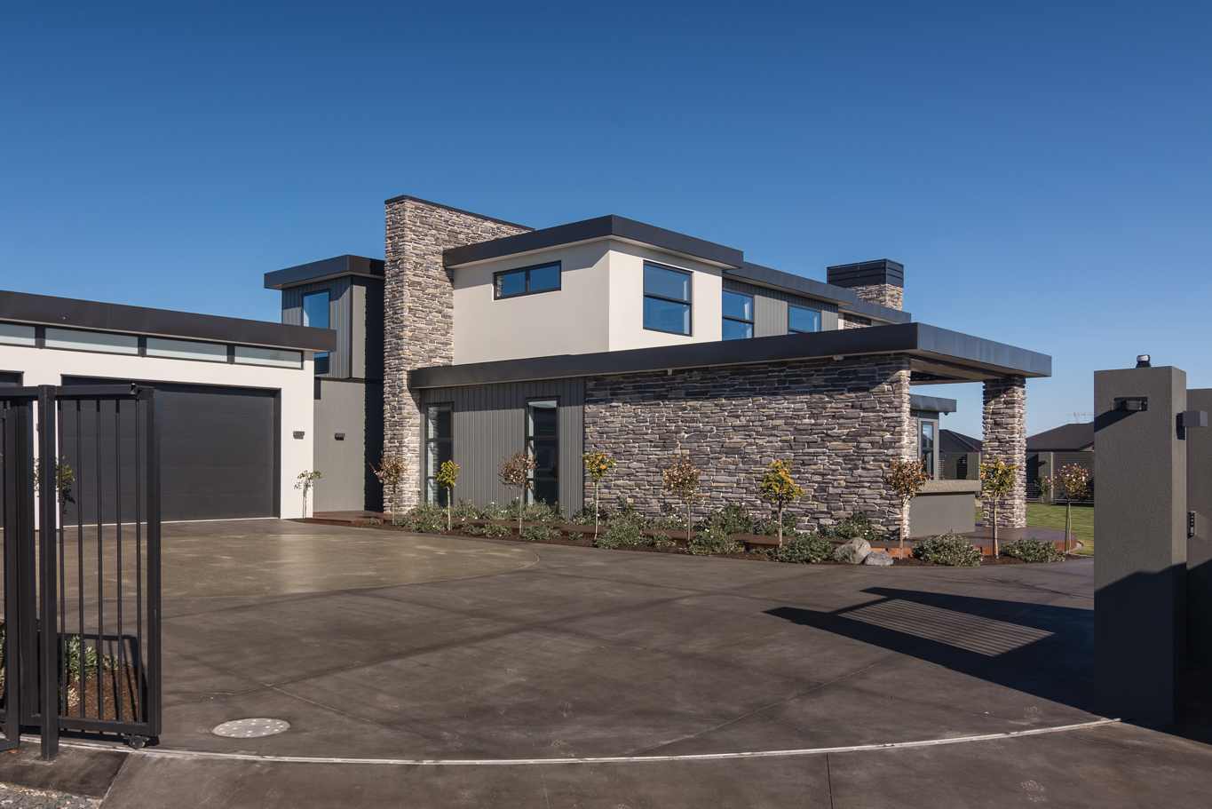 EXTERIOR:  The contrasting textures and colours of the exterior were achieved using Rockcote Integra, Hard as Rocks schist stone veneer and James Hardie Linea Oblique cladding.