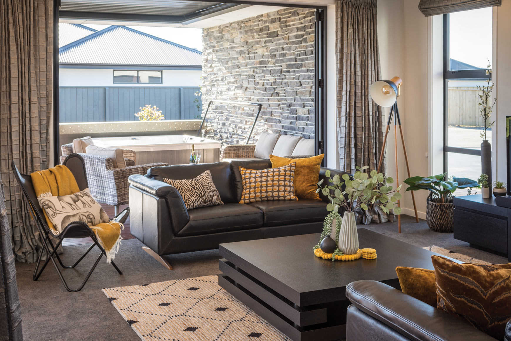 OUTDOOR LIVING:  Lay-back bifold doors create an easy flow from the living area to the spa and casual seating area, protected from the elements by the Stratco Allure Louvre system.