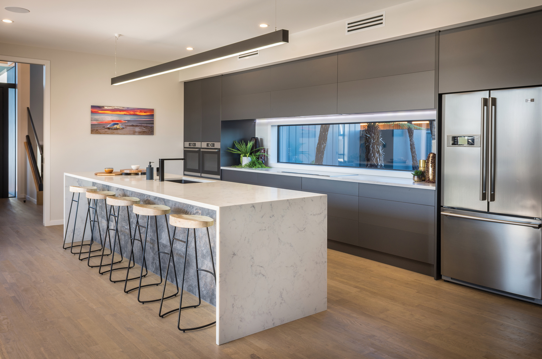 KITCHEN:  Misco Joinery supplied and installed the joinery in the beautiful and superbly functional kitchen which features a large kitchen island topped by a Prime Stone benchtop with waterfall ends.