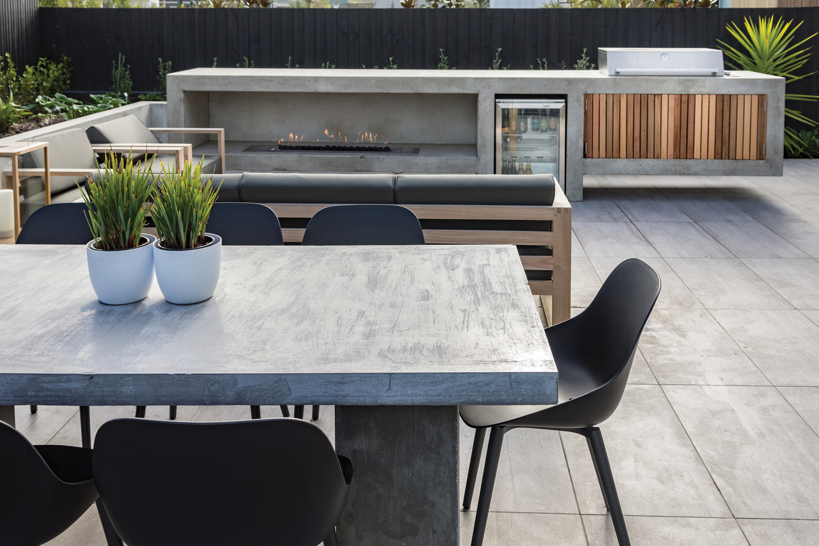 OUTDOOR LIVING:  Designed by Kamo Marsh Landscape Architects, the outdoor area combines technology, concrete structure and coastal planting, to create a fabulous sheltered space for entertaining.