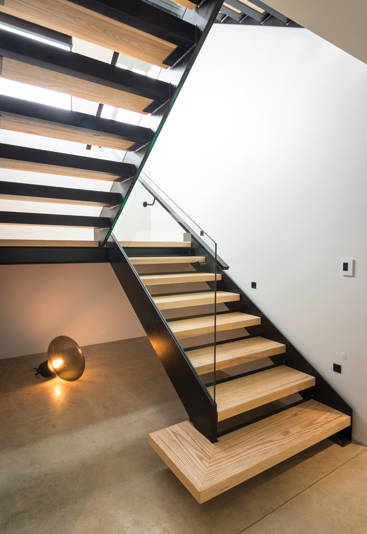 STAIRWELL:  Feature Brokis Muffin floor lamp from ECC in smoke grey glass. Custom-steel, frameless glass and laminated American oak staircase.