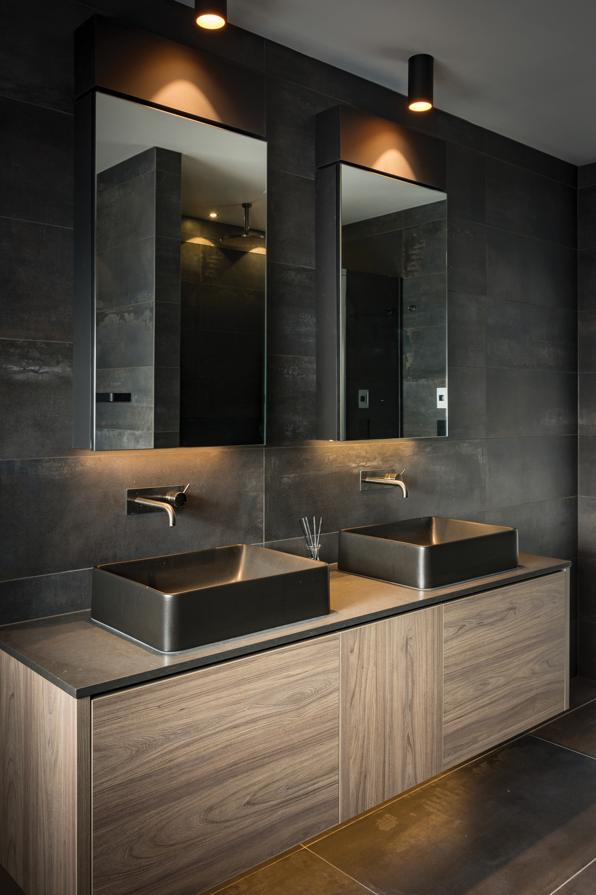 BATHROOM:  The boys' bathroom has Tondo rectangular Vessel basins in matte black with Buddy wall-mounted mixers in aged iron. The custom vanity is finished in Dusky Elm with benchtop in Caesarstone Raven.