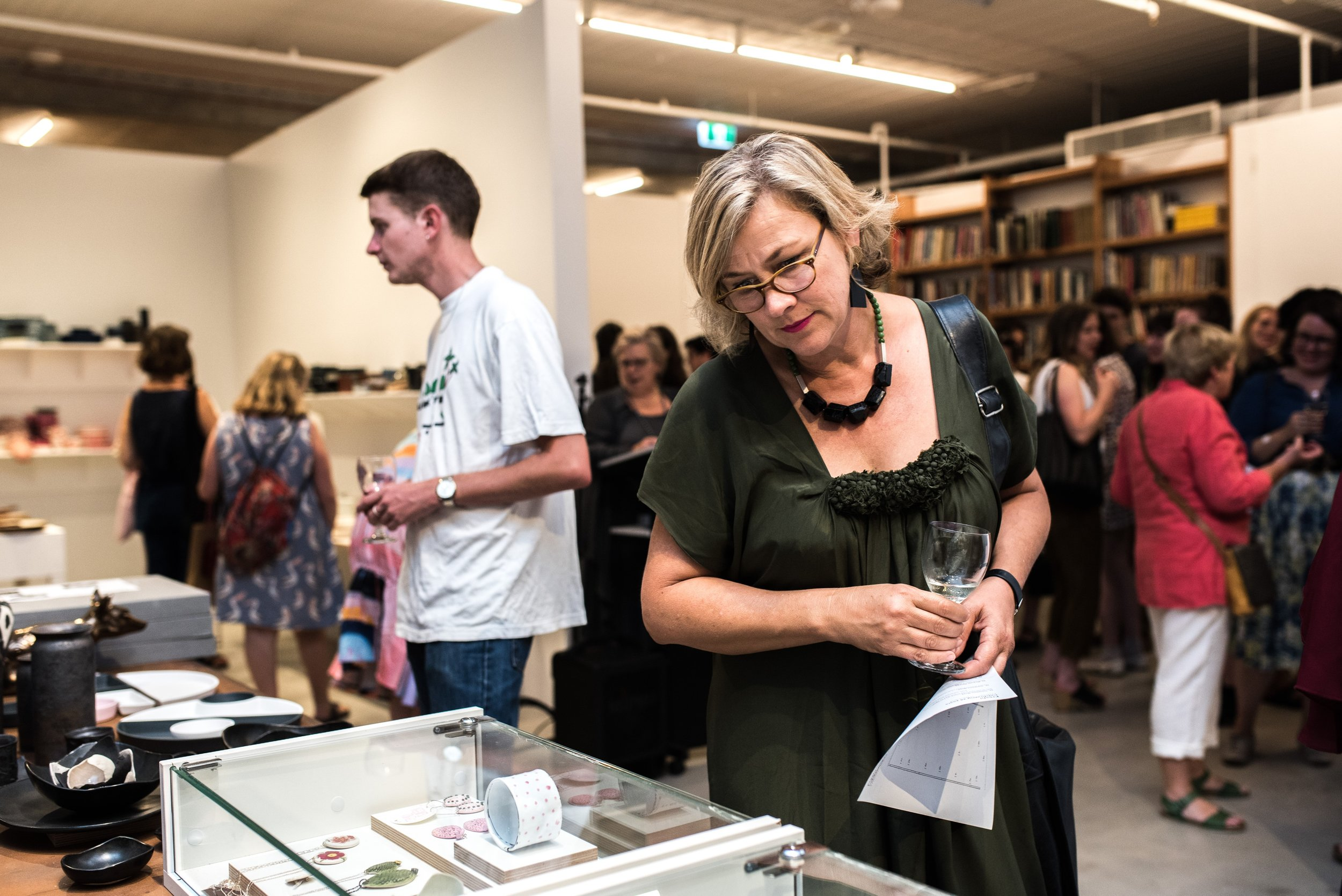 Guest exploring jewellery pieces from various artists featured at Craft Victoria.jpg