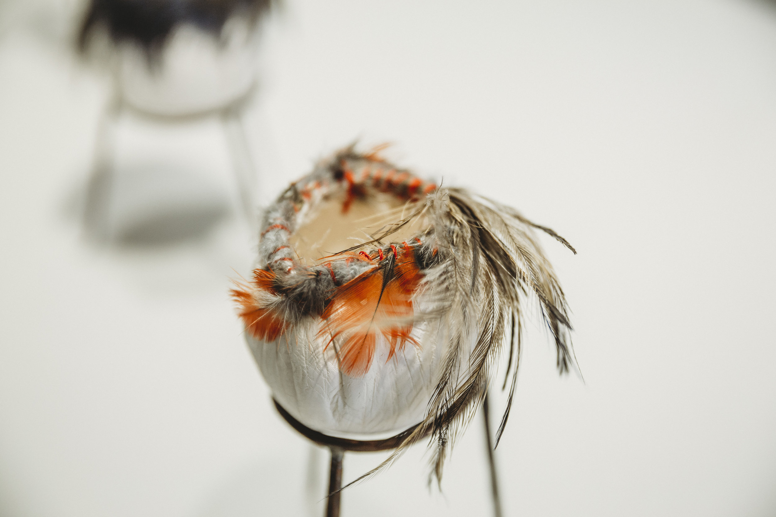 Lisa Waup,  Keeping Culture 5/7 , porcelain, Emu feathers, parrot feathers, cotton, hand forger copper railway waire, silver solder, 21 x 10 x 10 cm. Photography Amina Barolli