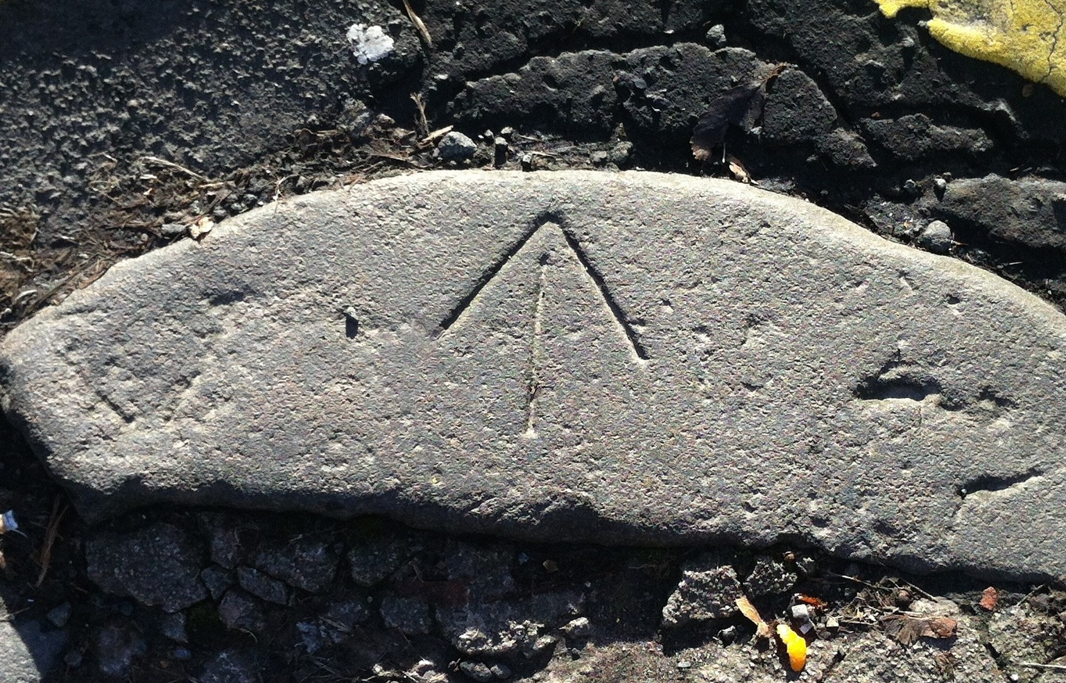 Located on University Avenue in Glasgow, Scotland this stone is on the tip of a right angle turn and points precisely to 45%. Essentially from this arrow the masons could sting a perfect right angle on the street corner.