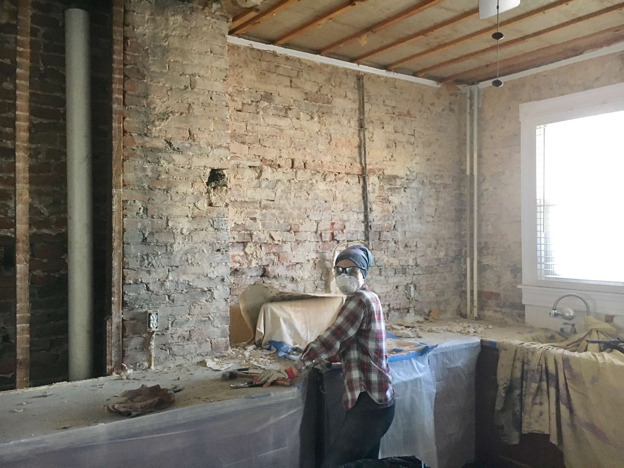 LOOK AT ALL THIS ORIGINAL BRICK WE UNCOVERED!!!! You can't see it due to the grime encrusted face mask, but I was smiling wide in this photo!