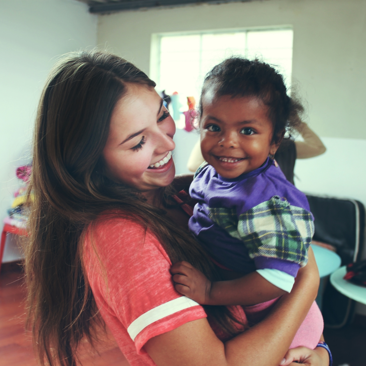 Volunteer with child, smiling