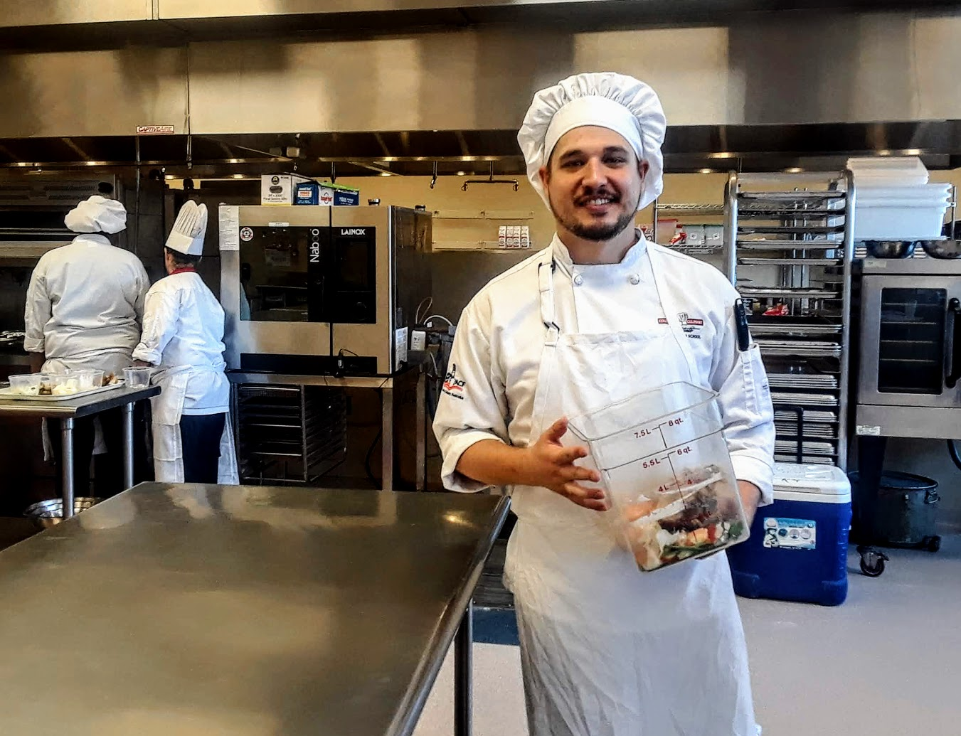A Columbus Culinary student shows off the class's container of food scraps