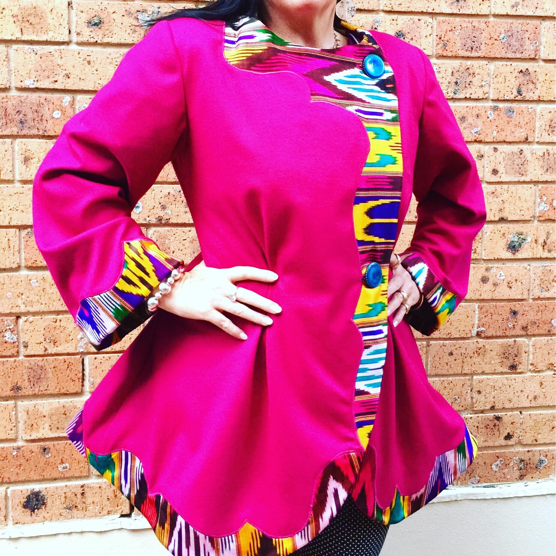 Katrina's Bright Pink Coat with Uzbekistani silk ikat appliqué detailing and bell sleeves.