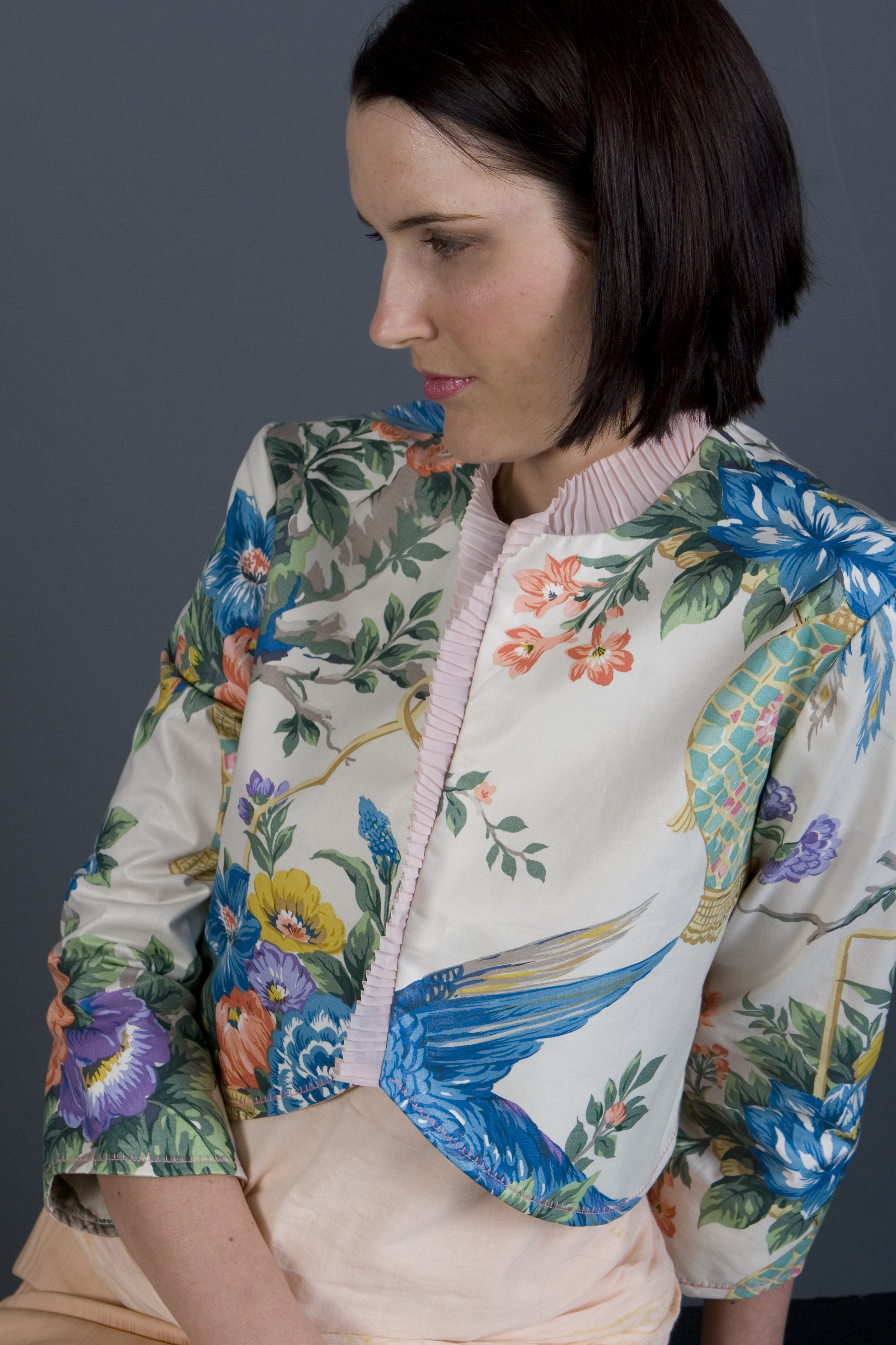 The Venus Bolero is a very unique design! It features a vintage print of flowers and bright birds on a cream background, with a pale pink vintage pleated organza trimming the front and neckline. To me this bolero has a little Oriental influence, mixed with a European influence... All the things I love.