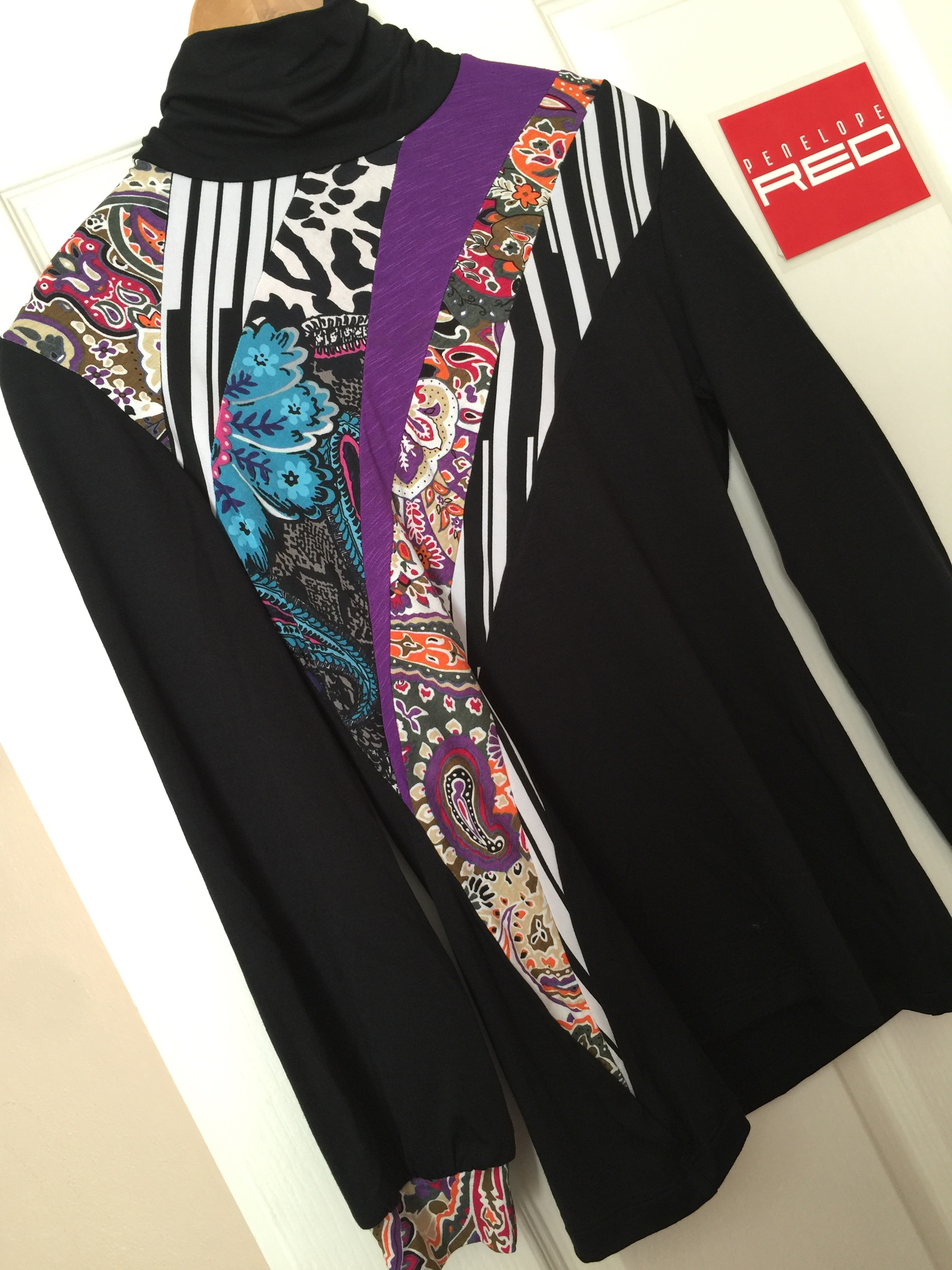 A black, white and paisley Jigsaw Skivvy. In this design the black, white and purple is the main focus. There are still many other colours in the design, but the focus is on the three main colours.