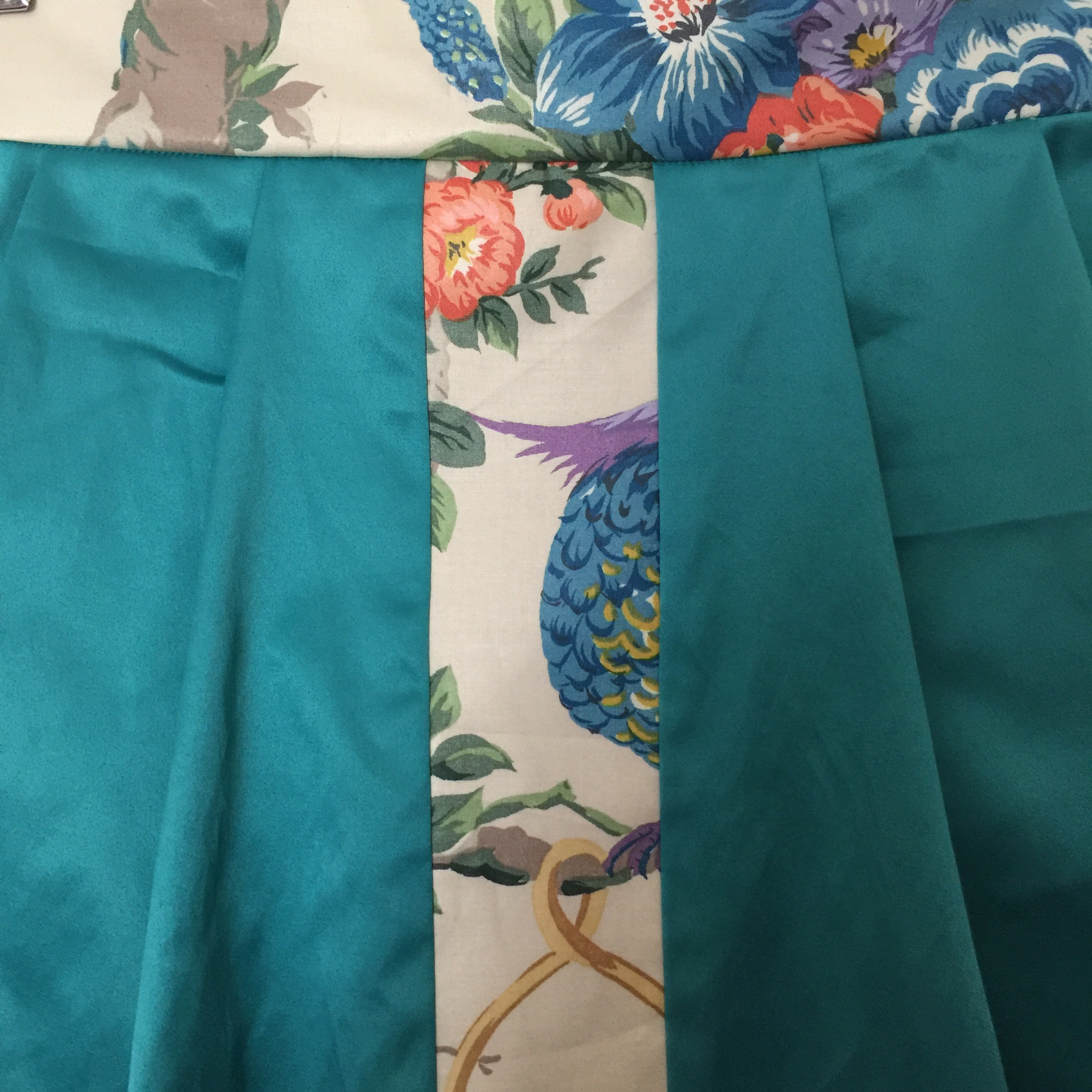 """A closeup of the Jade Pleated Skirt with A vintage """"Venus"""" Print."""