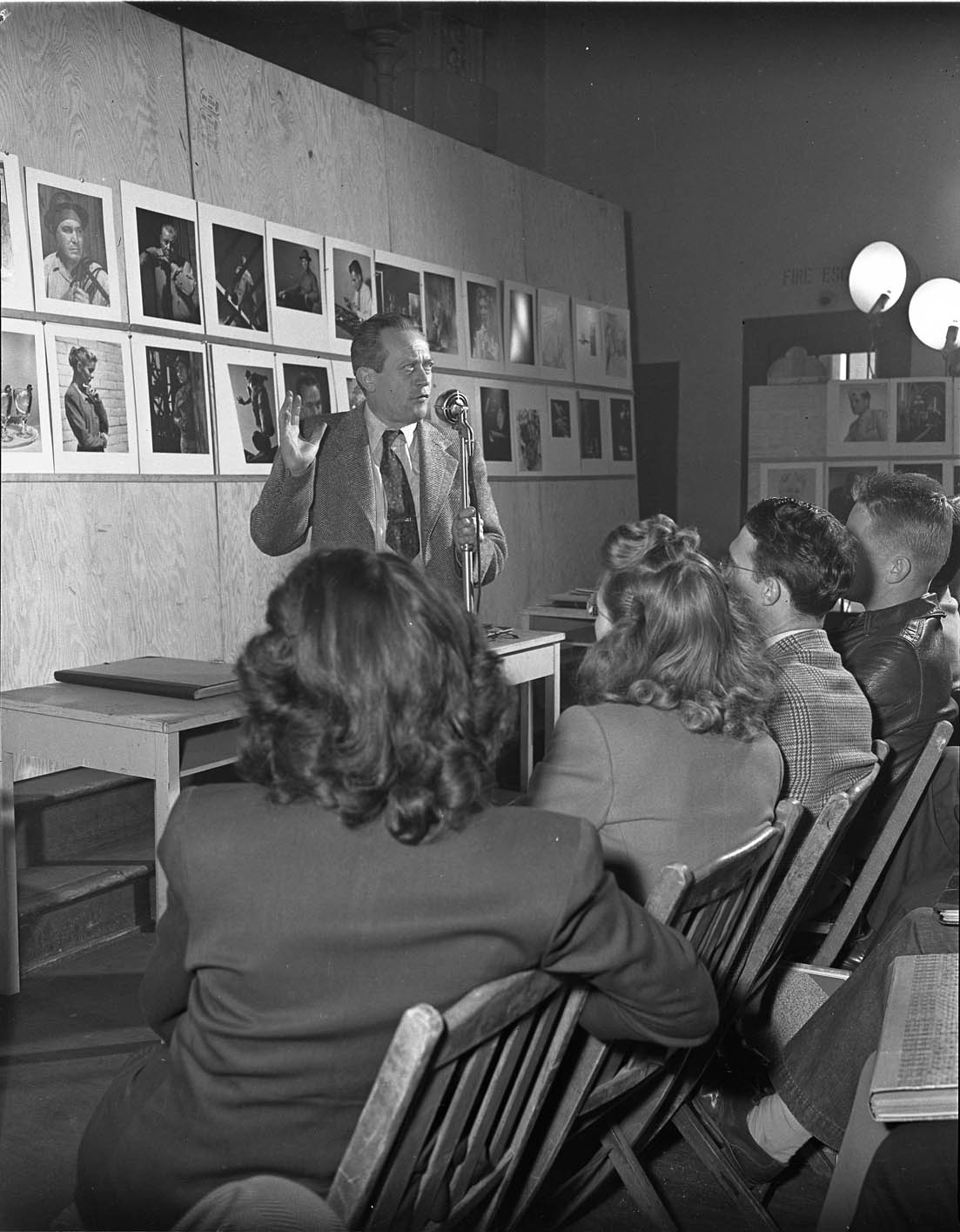 Drawing instructor Lorser Feitelson speaks in front of a classroom of students. Student work is displayed on the wall behind Feitelson, ca.1949-50.