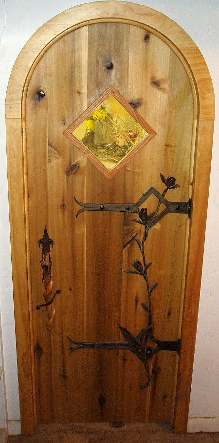 Yellow poplar door with a laminated archway and forged steel hinges, roses, and calla lily anchor flower.