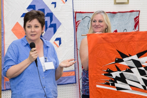 "Sharing about ""Bauhaus Birds in the Air"" which originated from a poster and was brought to pattern form by Adele. Quilt is held by ""Quiltin' Jenny."""