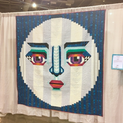 """""""Moonie McMoonface"""" by Melissa Averinos. Even if I hadn't talked to Melissa on the phone for an interview a few weeks ago, I think the name of this quilt would have tipped me off that we would get along splendidly. Though Melissa is best known for her raw-edge appliqué, this quilt is pieced. Also, if I were filthy rich, I would fly Melissa to my house for a week to give me private lessons of all three of her classes (the two on making faces and one on color)."""