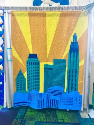 """""""Good Morning, Tulsa"""" by the Tulsa Modern Quilt Guild for the QuiltCon Charity Quilt Challenge. First off, I'm obsessed with the colors of the challenge this year, but I love that a guild not only conceived of this idea to capture their iconic skyline, but found a way to do it so cleanly and excellently. And the quilting is stunning, too-- I hope you can see it in the picture!"""
