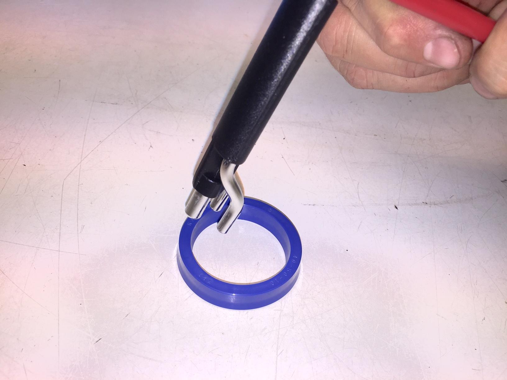 1, Fäst verktyget runt tätningens kant, två ben innanför och ett utanför kanten.
