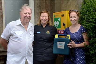 From left, Peter Coleman, Linda Richter and Katie Thomas by the defibrillator in its new position outside the box office door