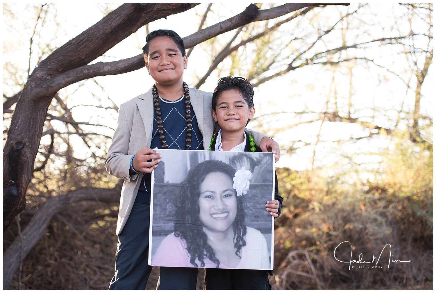 Mika and Niko holding a photo of their mom.
