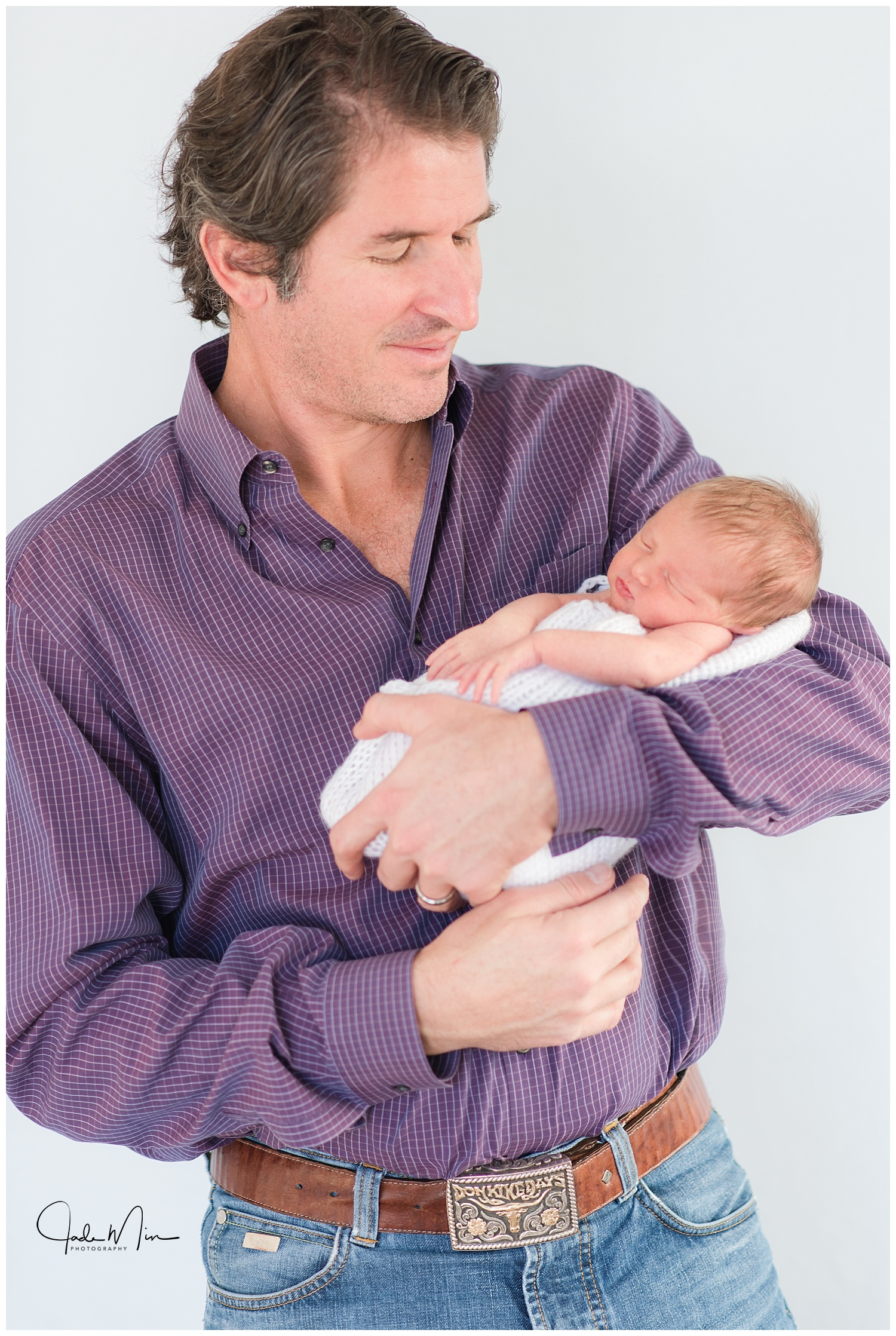 Baby Amelia being held by proud daddy during the newborn session at the Florez family home in Scottsdale, Arizona.