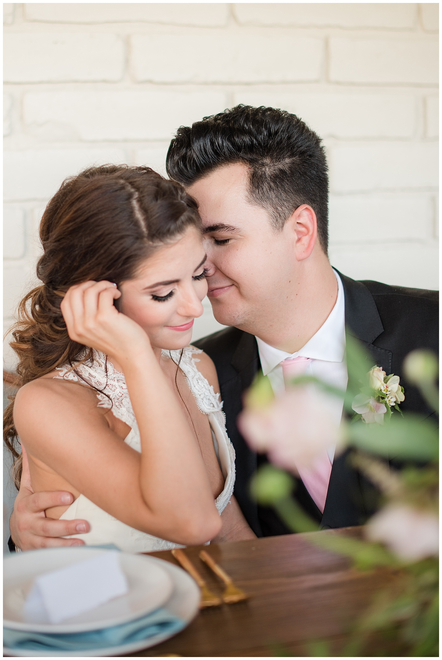 Bride Jessica wearing dress provided by Bella Lily Bridal in Phoenix and nuzzling with groom Slaven, photographed at Gather Estate in Mesa, Arizona.