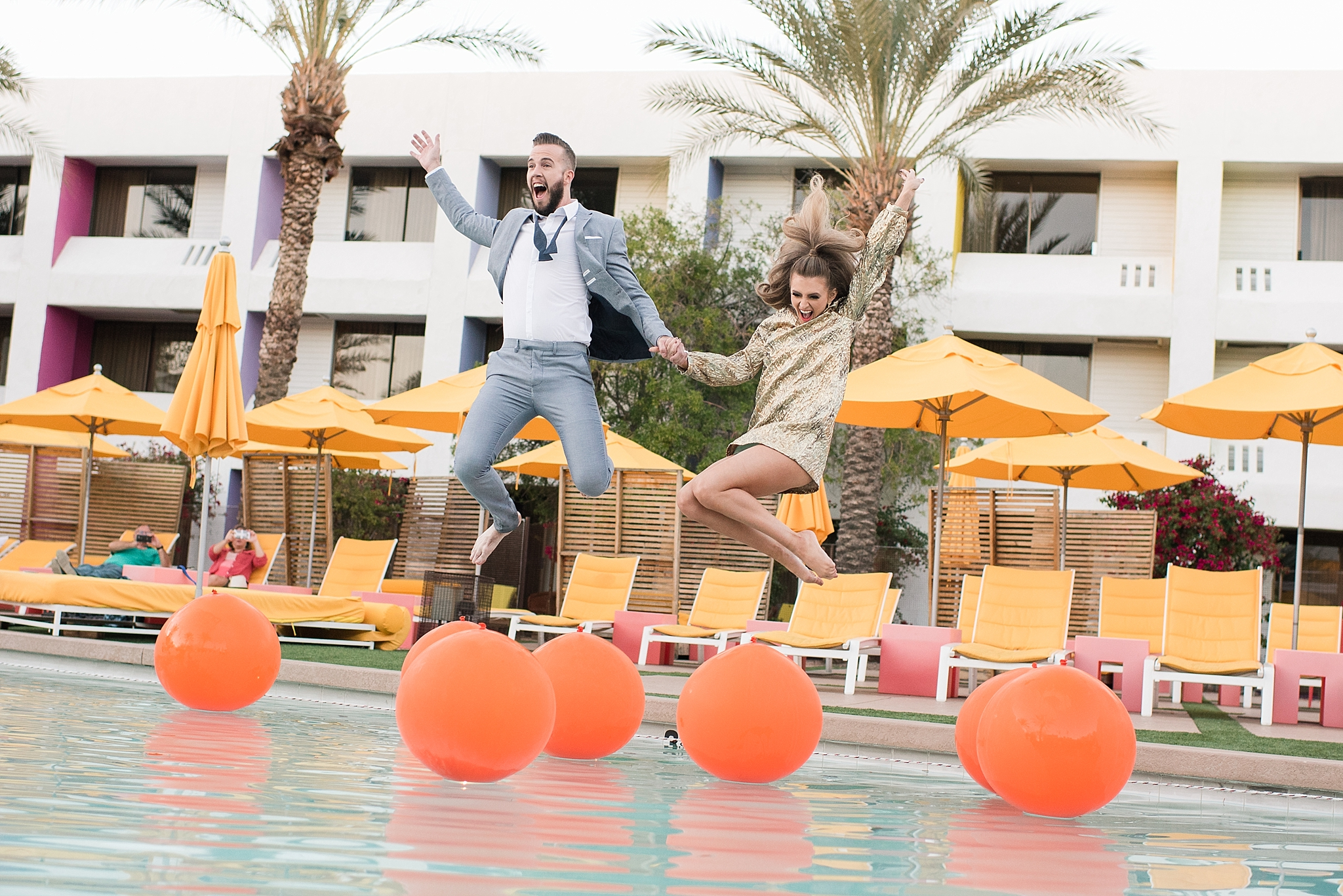 Bride Natalie Meyer jumping into The Saguaro Scottsdale's pool with her groom Zach Meyer. Hair and makeup was done by Makiaj Beauty. Groom's suit provided by Magro Clothing. Photos by Jade Min Photography.