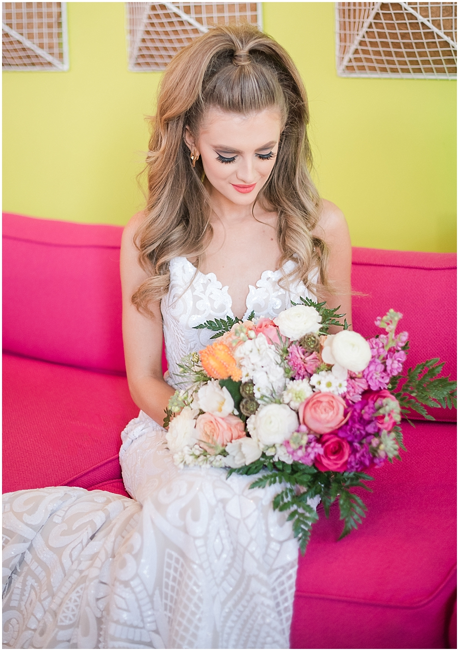 Gorgeous bride Natalie Meyer posing in a dress by Bella Lily Bridal, no a settee at the 'Party Like There's No Saguaro' photo shoot at The Saguaro Scottsdale. Photos by Jade Min Photography.