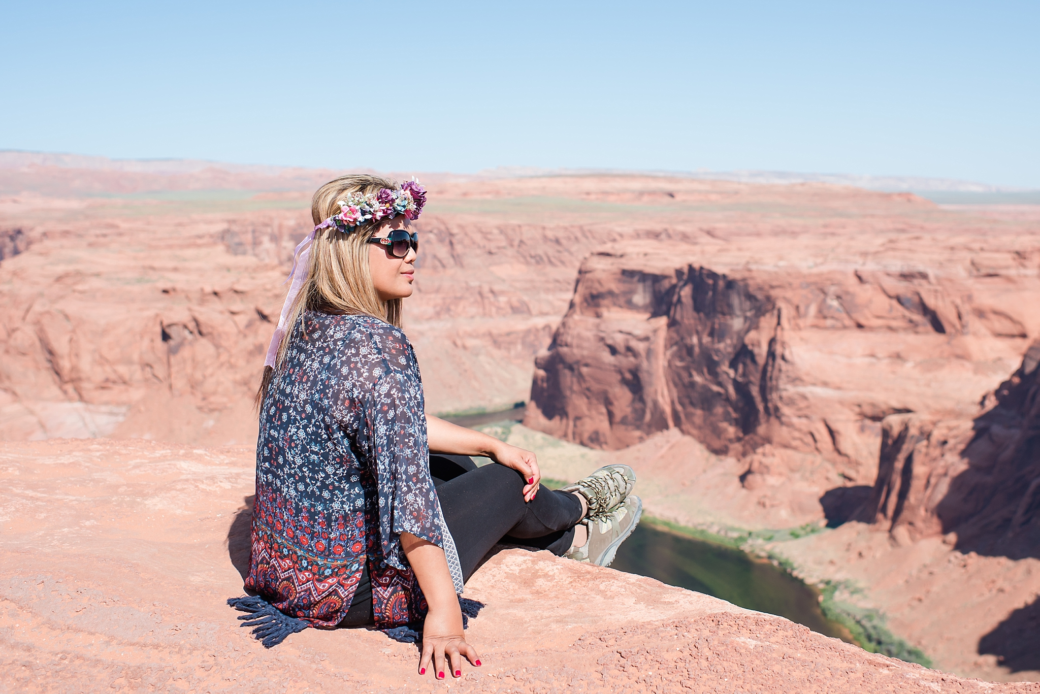 Jade trying not to fall off while sitting on the edge of the precipice at Horseshoe Bend during late morning near Page, Arizona. Travel photo by Jade Min Photography.