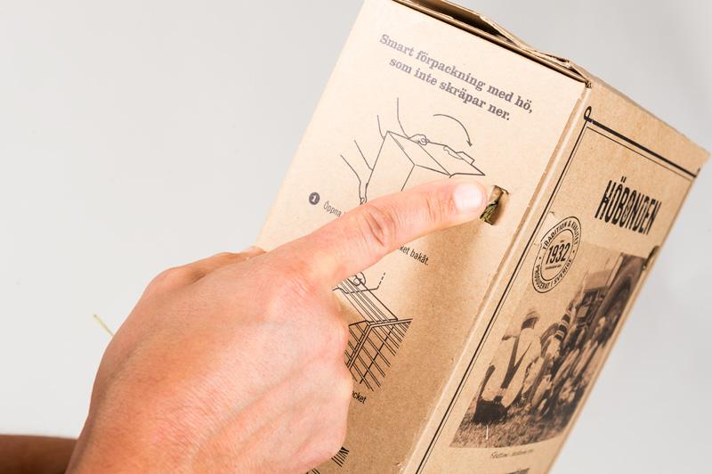 Tryck in dom utstansade hålen på baksidan av kartongen