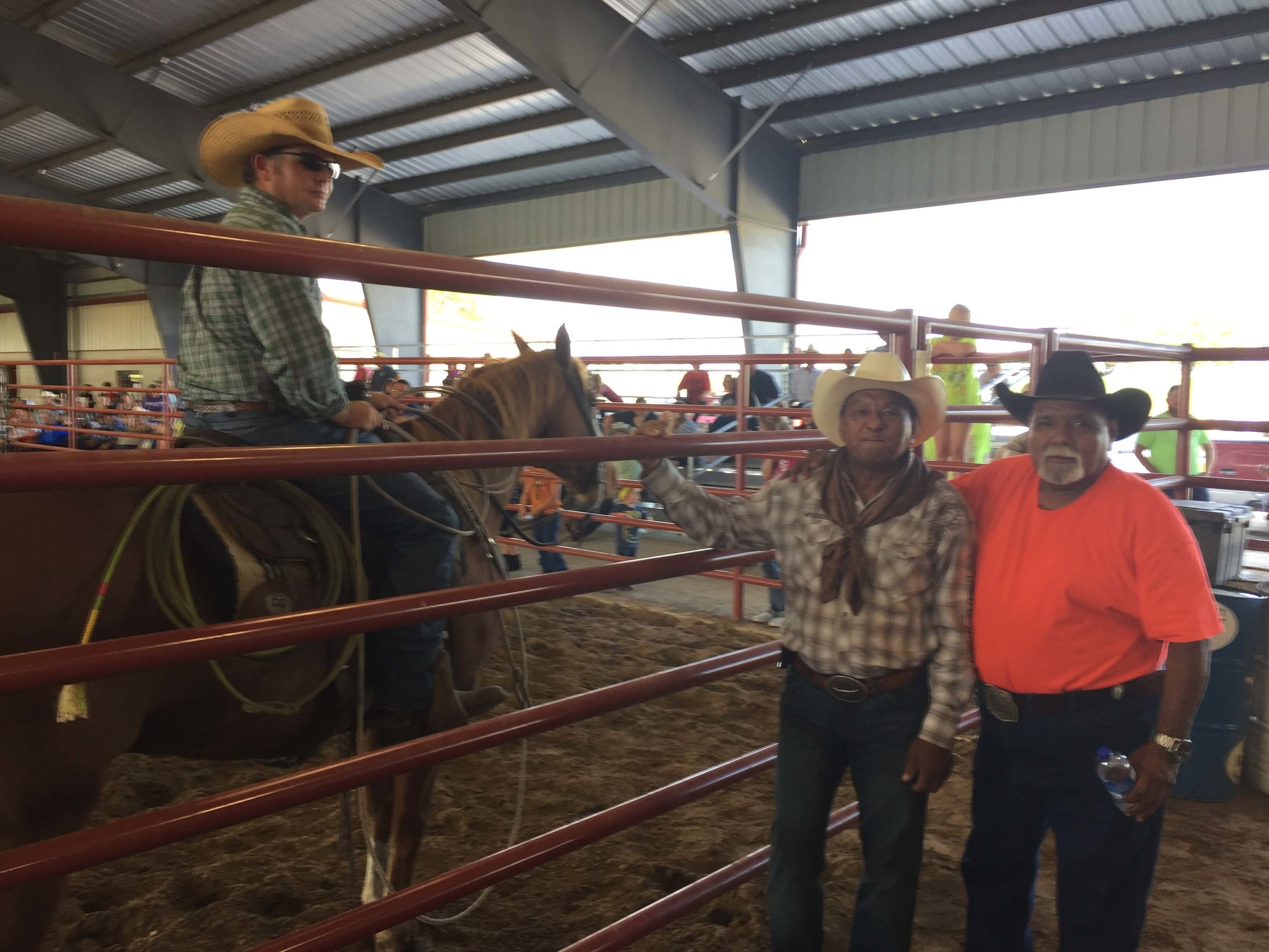 Frank Milano (orange shirt) and Alfredo Andrade (of Honduras) talk with Nick Gas (cowboy pastor and horse trainer) in a break in the action at the Denton County bull riding event put on in honor of Alfredo's son, Sergio,who was a professional bull rider and friend of ours who was murdered a couple of years ago.