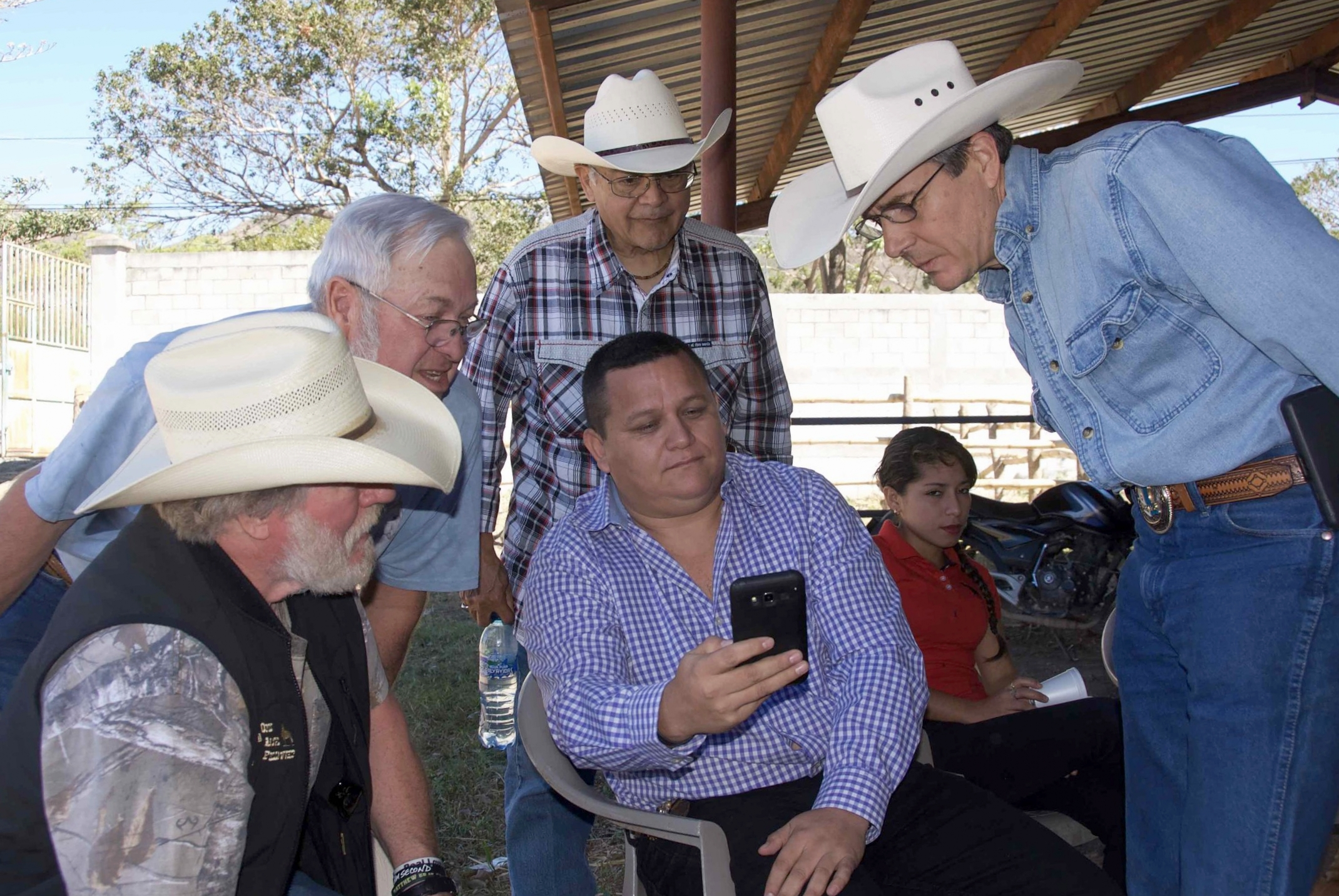 US cowboys enjoy seeing personal horse photos on the phone of a Guatemalan cowboy (and town lawyer) before a dairy co-op tour and lunch meeting with a womens' group.