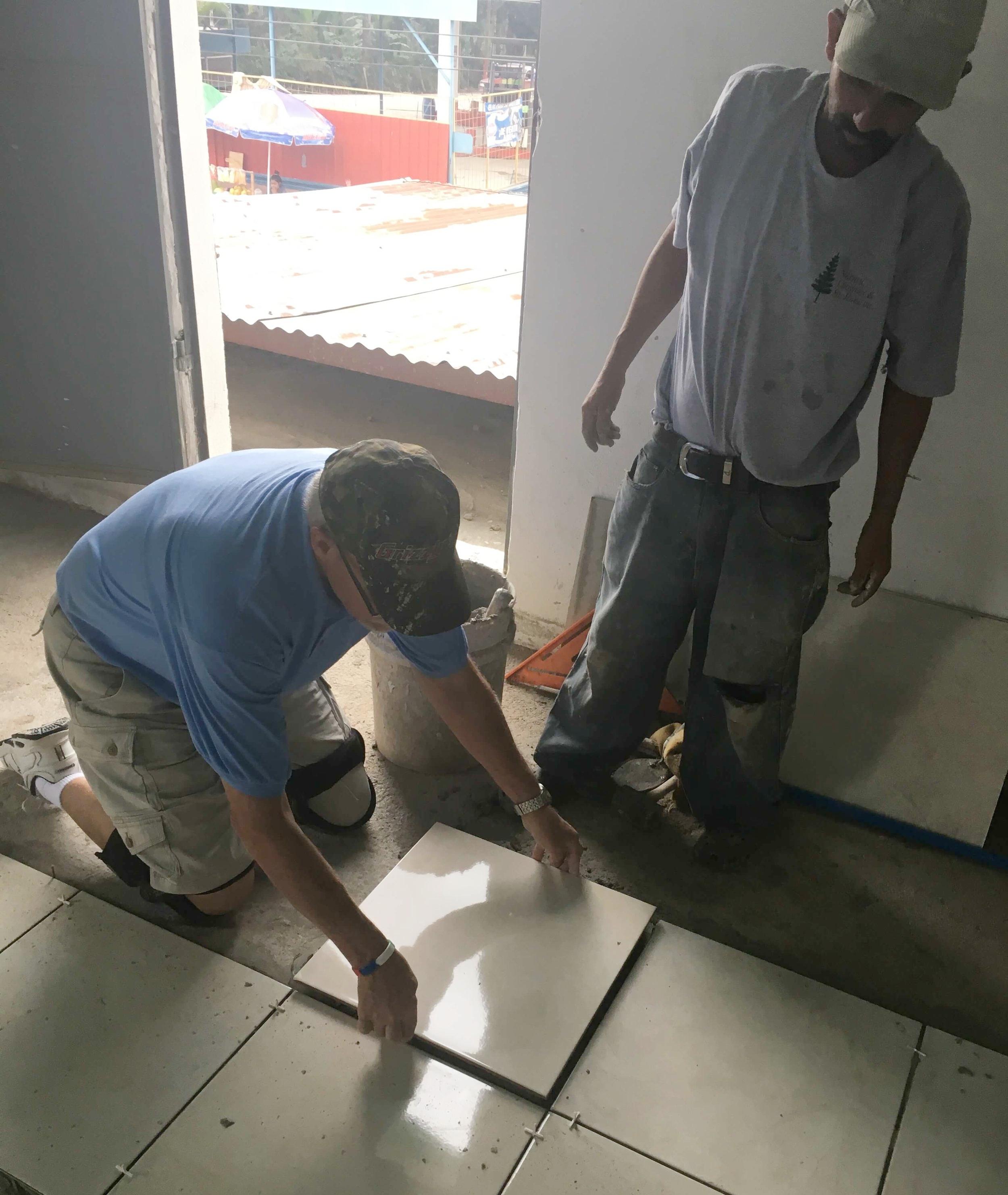 Dean Kucharski lays tile while a Guatemalan team member looks on.