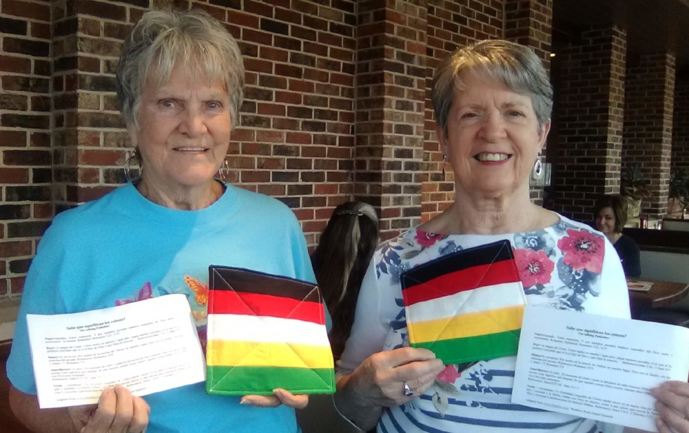 """Janice Brite and Virginia Jones hold up two of the 135 """"talking"""" potholders they made for our ladies mission team to use in Guatemala in January 2018. The colors help people share the gospel, and the sheets are the printed Spanish version of the message."""