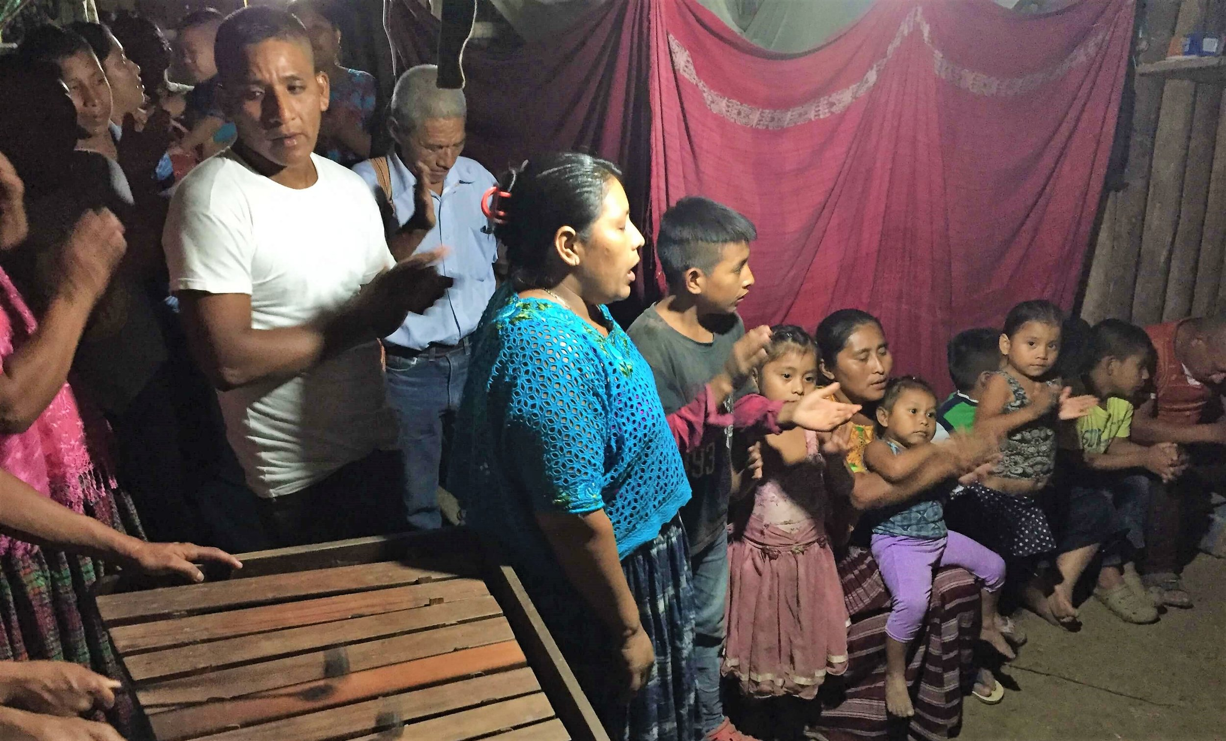 Aníbal (white shirt), pastor in Sejux, and his new congregation sing praises.