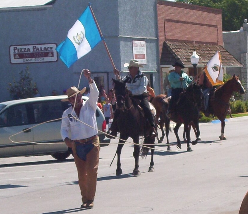 Oscar, a trick roper, leads the Guatemala delegation in the Burwell, Nebraska parade. Rolando is carrying the Guatemala flag on horseback.