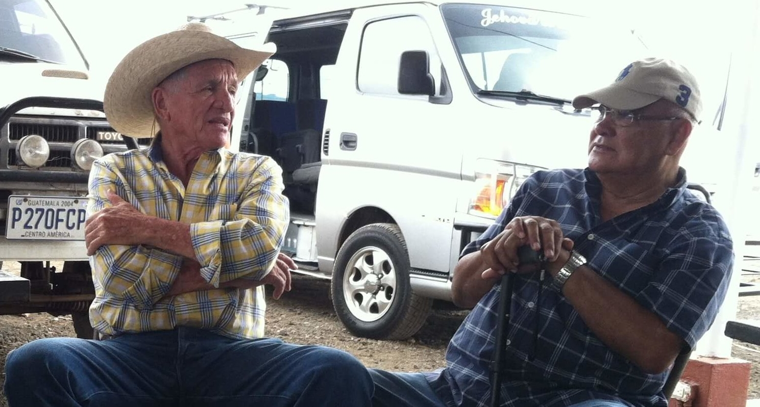 Two friends converse at a cattle sale in Guatemala.