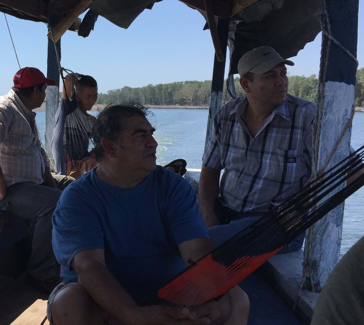 Cesar (seated in the hammock) speaks with Manuel on a boat trip to explore a protected river canal that is being negatively affected by trash.