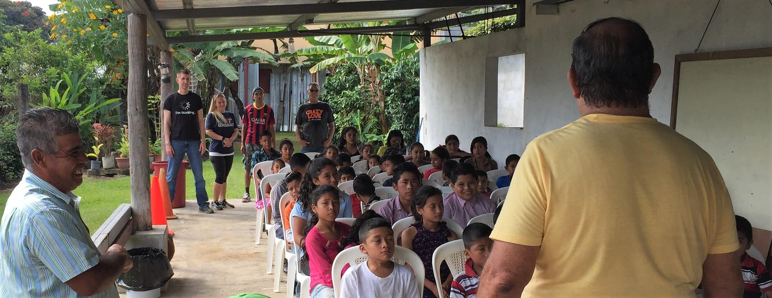 About 60 children came for our children's event at Cesar's house. Here they sat for instructions before breaking into three groups.